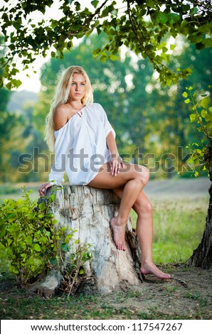 Portrait of young beautiful blonde  woman wearing white  dress, sitting on stump against lake at summer green park.fashion portrait of sexy young woman sitting on stump in the forest .