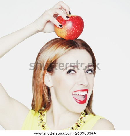 Portrait of young beautiful blonde woman with an apple on her head - stock photo