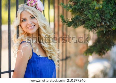 Portrait of young beautiful blonde woman with bare shoulders , on green background summer nature.
