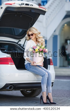 portrait of young beautiful blonde woman with box of flowers by car. flowers in box. spring time outdoor photo. bouquet of flowers in gift box. birthday, March 8, Valentine's Day, romantic - stock photo