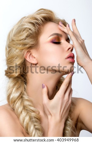 Portrait of young beautiful blonde woman with creative make-up and french braids touching her face. Multicolored smokey eyes. Modern makeup, hairdressing or skincare concept - stock photo