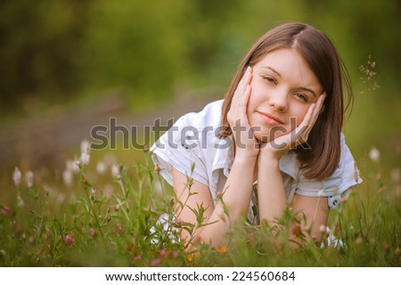 Portrait of young beautiful brunette girl lying on grass at summer green park and propping up her face.