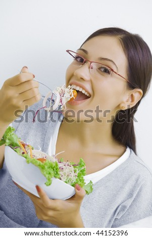 Portrait of young beautiful brunette with vegetable salad - stock photo