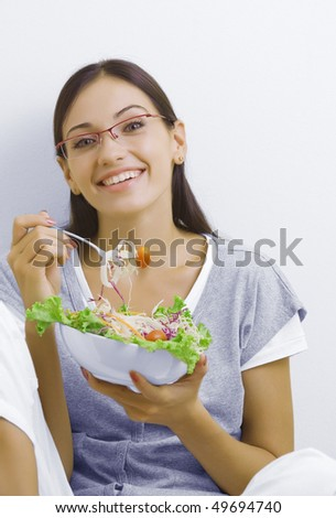 Portrait of young beautiful brunette with vegetable salad