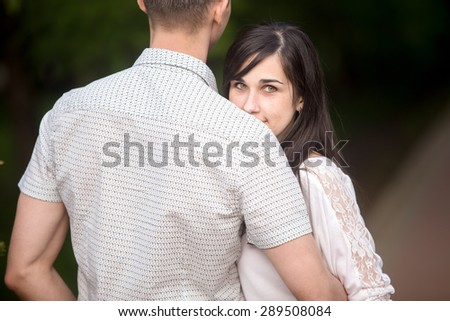 Portrait of young beautiful brunette woman cuddling with her boyfriend, hiding behind his shoulder with happy shy smile - stock photo