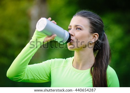 Portrait of young beautiful brunette woman drinking water, outdoor