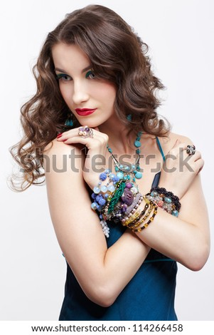portrait of young beautiful brunette woman in blue dress and jewellery - stock photo