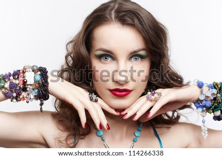 portrait of young beautiful brunette woman in blue dress and jewellery touching her face with manicured hands - stock photo