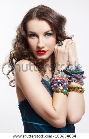portrait of young beautiful brunette woman in blue dress, bracelets, rings, ear-rings and beads - stock photo