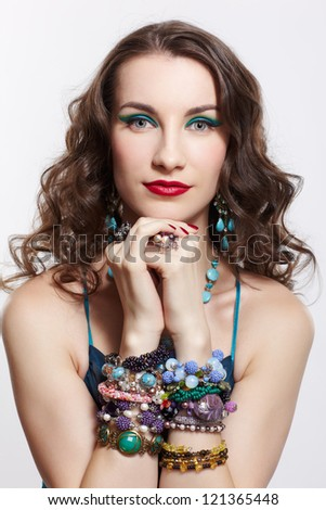 portrait of young beautiful brunette woman in blue dress, in beads, rings, ear-rings and bracelets posing on gray