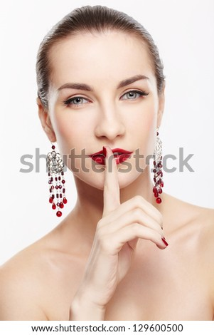 portrait of young beautiful brunette woman in ear-rings asking to be quiet - stock photo