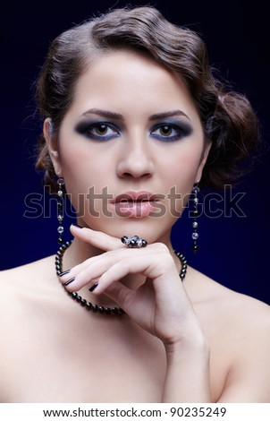 portrait of young beautiful brunette woman in ear-rings, beads and ring - stock photo