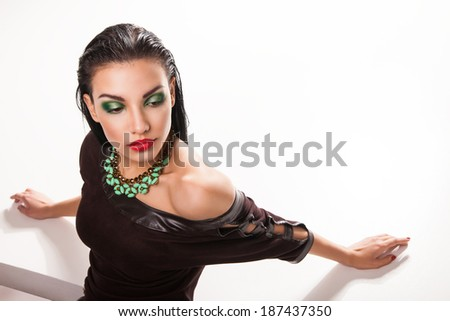 portrait of young beautiful brunette woman in jewellery laying over white background - stock photo