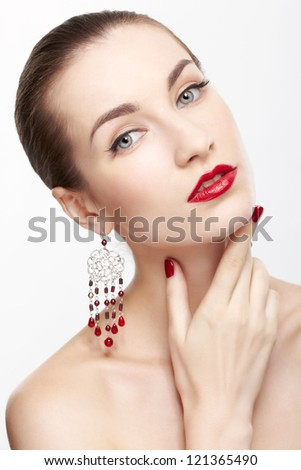 portrait of young beautiful brunette woman in jewellery on gray touching neck - stock photo