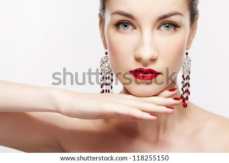 portrait of young beautiful brunette woman in jewellery on gray with manicured hand under her chin - stock photo