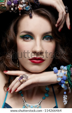 portrait of young beautiful brunette woman in jewelry on black touching her chin and hair - stock photo