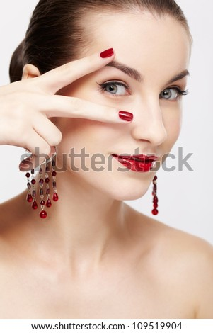 portrait of young beautiful brunette woman in jewelry on gray - stock photo