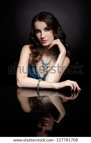 portrait of young beautiful brunette woman in jewelry sitting at reflecting table - stock photo