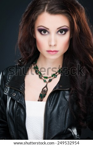 Portrait of young beautiful brunette woman in jewelry standing over grey background. Vogue style. Studio shot. Perfect makeup, hair and skin. - stock photo