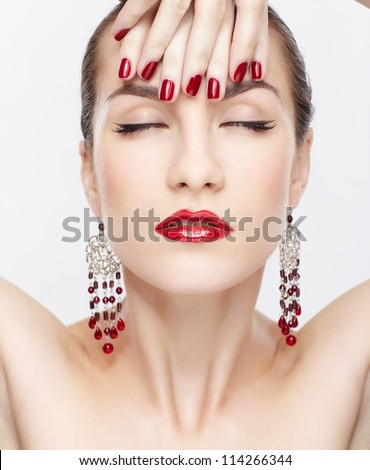 portrait of young beautiful brunette woman in jewelry touching her forehead with manicured hand - stock photo