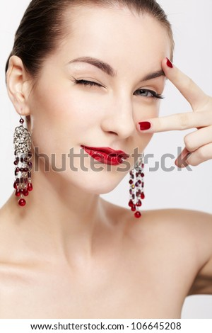 portrait of young beautiful brunette woman in jewelry winking - stock photo