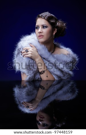 portrait of young beautiful brunette woman in mantlet and jewellery at mirror table - stock photo