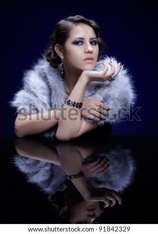 portrait of young beautiful brunette woman in mantlet and jewelry at mirror table - stock photo