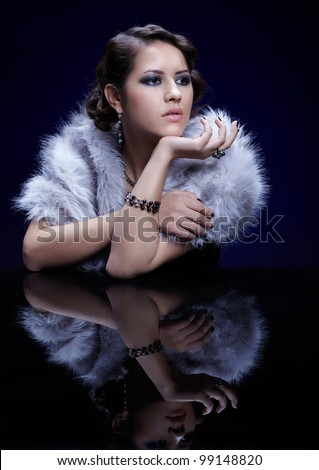 portrait of young beautiful brunette woman in mantlet and jewelry at reflecting table - stock photo