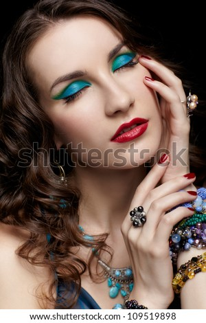 portrait of young beautiful brunette woman in ring, bracelet and beads closing eyes