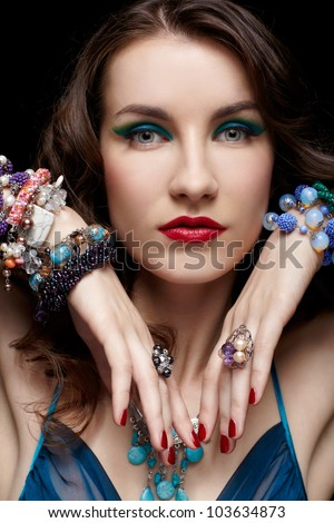 portrait of young beautiful brunette woman in rings, bracelets and beads on black