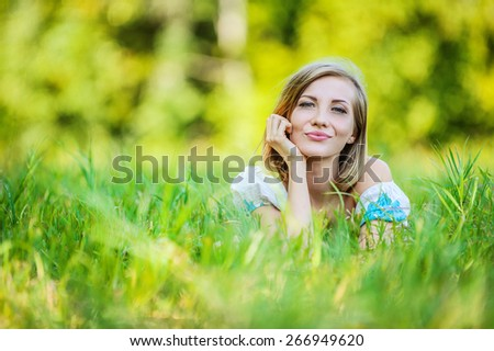 Portrait of young beautiful brunette woman lying on grass and propping up her face at summer green park. - stock photo