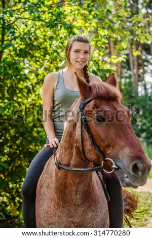 Portrait of young beautiful brunette woman riding horse at summer green forest.