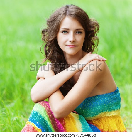 Portrait of young beautiful brunette woman wearing colourful bright dress, sitting on grass at summer green park. - stock photo