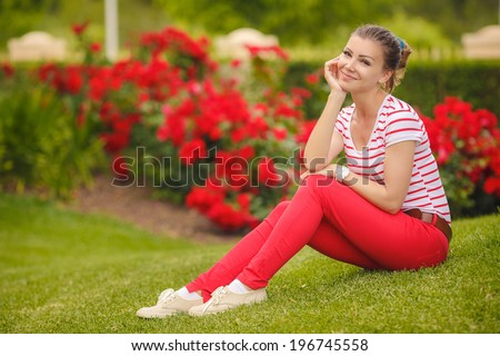 Portrait of young beautiful brunette woman wearing colourful bright t-short and red trousers, sitting on grass at summer green park. - stock photo