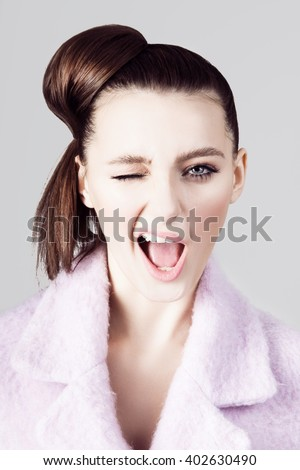 Portrait of young beautiful brunette woman winking, smiling. Pastel colors. - stock photo