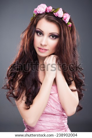 Portrait of young beautiful brunette woman with flowers on her head standing over grey background. Vogue style. Studio shot. Perfect makeup, hair and skin. - stock photo