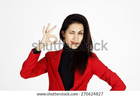 Portrait of young beautiful business woman in red jacket showing showing hand ok sign