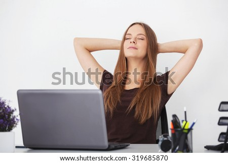 Portrait of young beautiful business woman relaxing at office. - stock photo