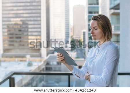 Portrait of young beautiful businesswoman in white shirt using modern tablet outdoors, Tablet on city background, Flare light, Shallow DOF.