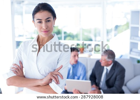 Portrait of young beautiful businesswoman with arms crossed at office - stock photo