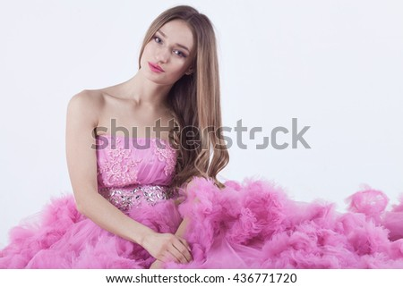 Portrait of young beautiful caucasian blonde in gorgeous pink dress on white background - stock photo