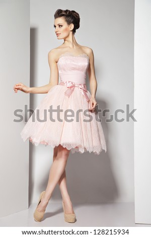 Portrait of young beautiful caucasian brunette in gorgeous dress on white background - stock photo