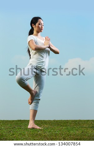 Portrait of young beautiful Chinese woman meditating and in a yoga pose on grass - stock photo