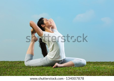 Portrait of young beautiful Chinese woman sitting meditating and in a yoga pose on grass - stock photo