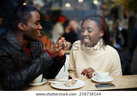 Portrait of young beautiful couple in love having coffee in beautiful cafe, two young people in cafe enjoying the time spending with each other - stock photo
