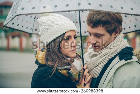Portrait of young beautiful couple in love looking under the umbrella in an autumn rainy day. Love and couple relationships concept. - stock photo