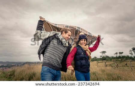 Portrait of young beautiful couple playing outdoors with blanket in a windy day over dark cloudy sky - stock photo