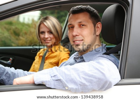 Portrait of young beautiful  couple sitting in the car