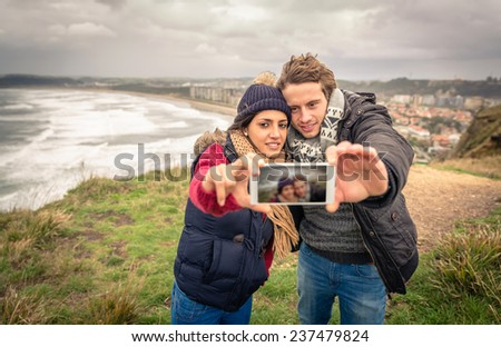 Portrait of young beautiful couple taking selfie photo in a smartphone with sea and dark cloudy sky on the background - stock photo