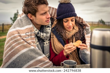 Portrait of young beautiful couple under blanket eating muffin in a cold day with sea and dark cloudy sky on the background - stock photo